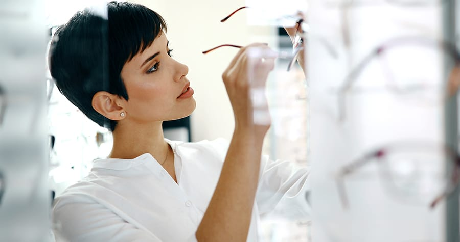 beautiful short haired woman selecting a pair of eye glasses
