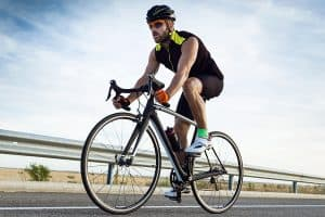 man riding a bicycle on the road wearing sunglasses