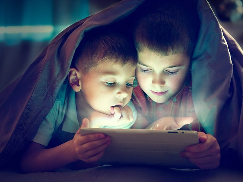 Two children lying in bed reading from a computer tablet