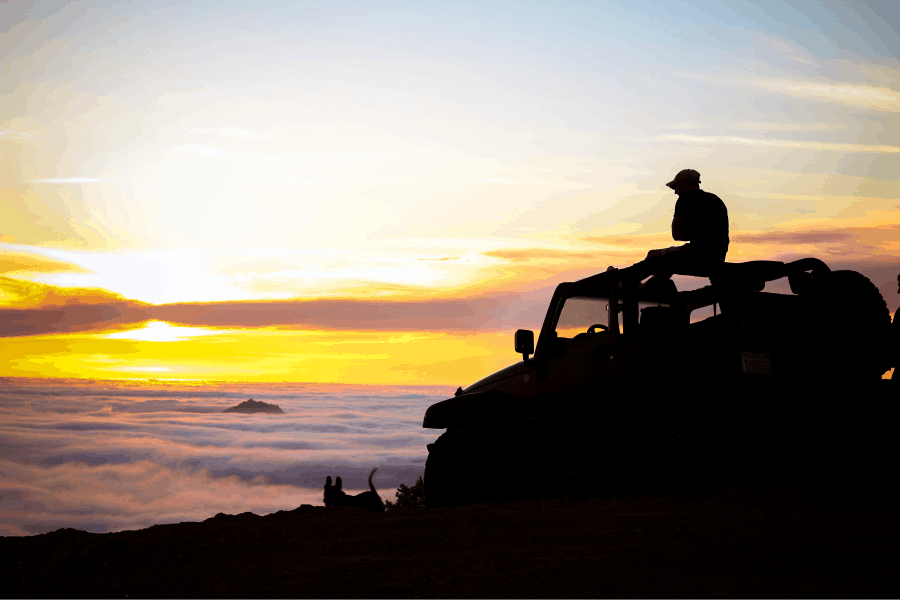 Man sitting on the roof of his Jeep viewing the sunset