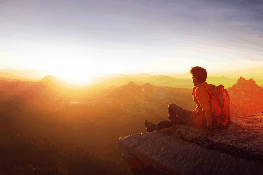 Man sitting on mountain viewing a beautiful sunset with orange Sky