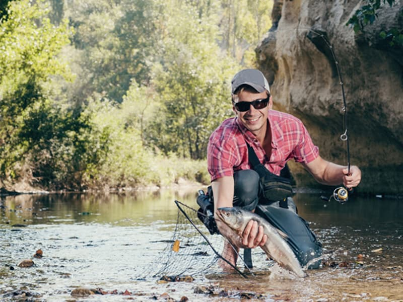 A man fishing in a river wearing sunglasses