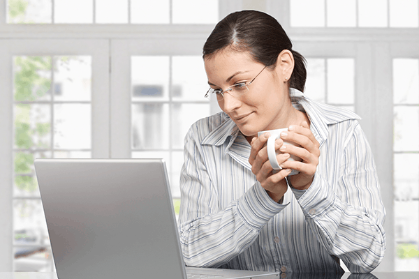 a woman wearing glasses looking at her laptop