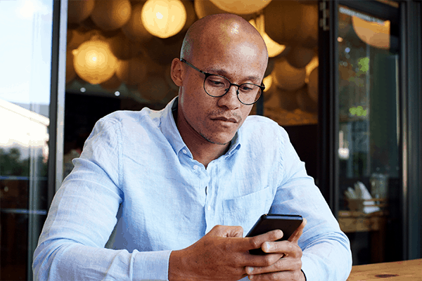 a young man wearing glasses typing on his phone