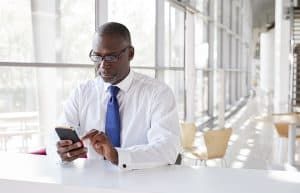 a man wearing glasses looking seriously at his phone