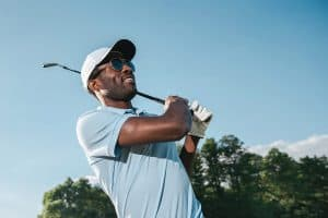 an african male wearing sunglasses while playing golf