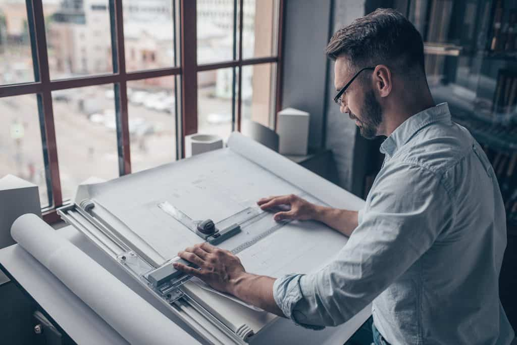 architect wearing glasses, working at a drawing table