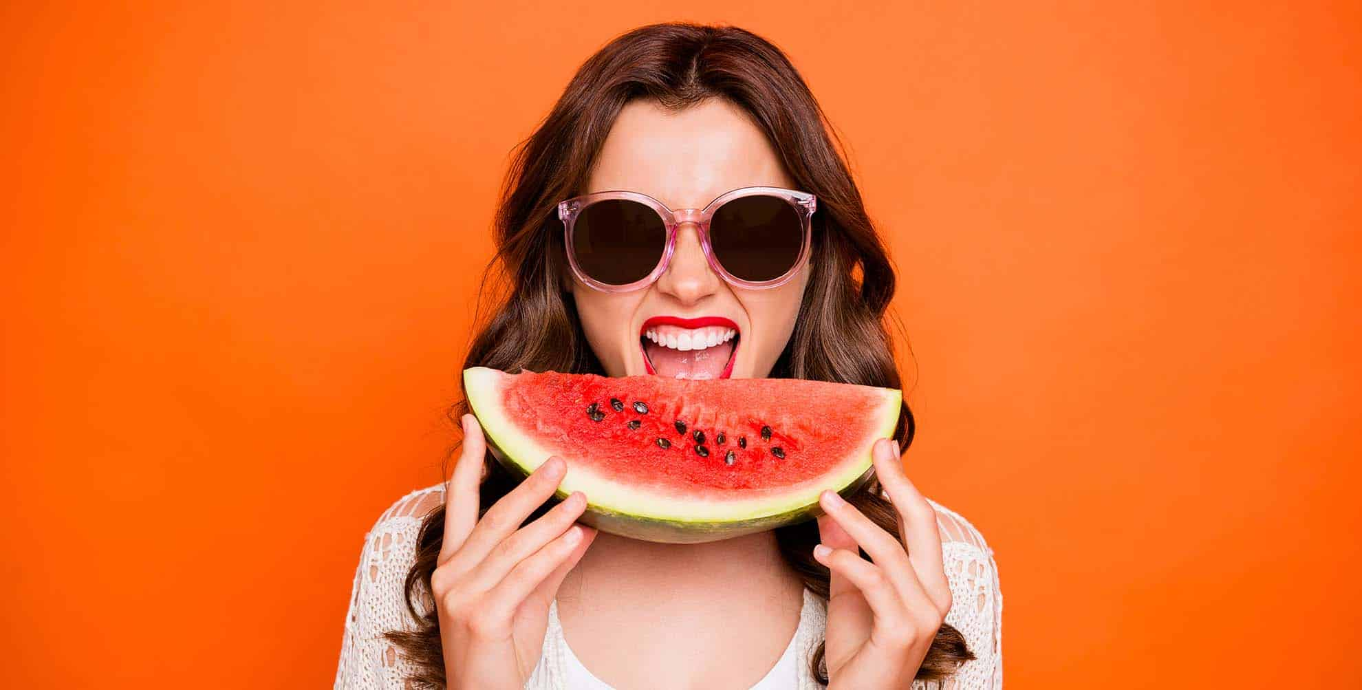 pretty lady wearing sunglasses eating a watermelon